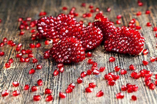 Плод разделен на части с семенами, вкусными красными зернами спелого граната, кисло-сладким вкусом здорового плода гранатового дерева.