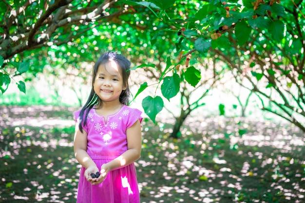 庭の小さな女の子の手に桑の実