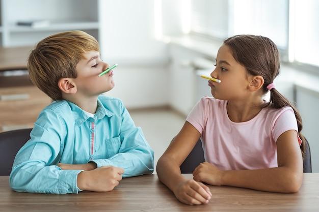 Забавный мальчик и девочка, играющие за столом