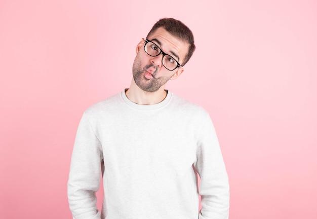 面白いコメディアンは、学校の一日の後に浮気して、彼の目を交差させています。ピンクで一人で楽しんでいるぎこちない表情のグーフィーオタク