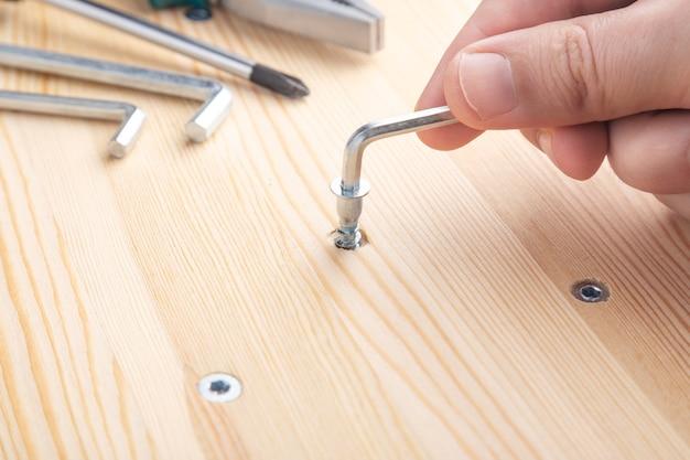가구 조립자는 육각 렌치로 캠 볼트를 조입니다.