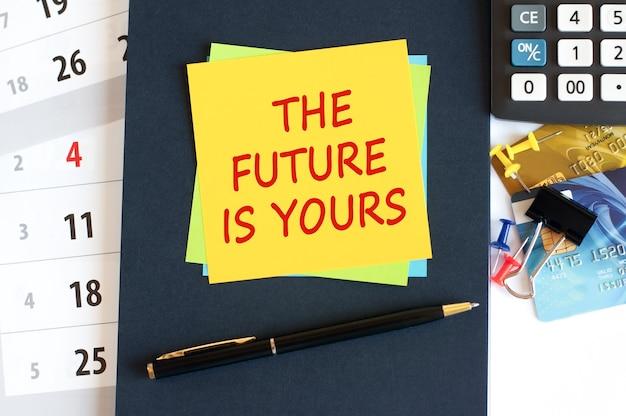 未来はあなたのものです、青い背景の黄色い紙の正方形の形のテキスト。デスクトップ上のメモ帳、電卓、クレジットカード、ペン、文房具。ビジネス、財務の概念。セレクティブフォーカス。