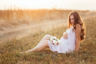 The future mother sitting on the grass