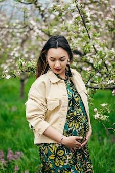 미래의 어머니는 피는 나무가있는 정원에 서 있습니다.