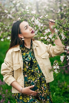 未来のお母さんは木々が咲く庭に立っています