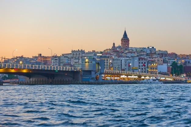 Галатский мост через бухту золотой рог в стамбуле ночью, турция