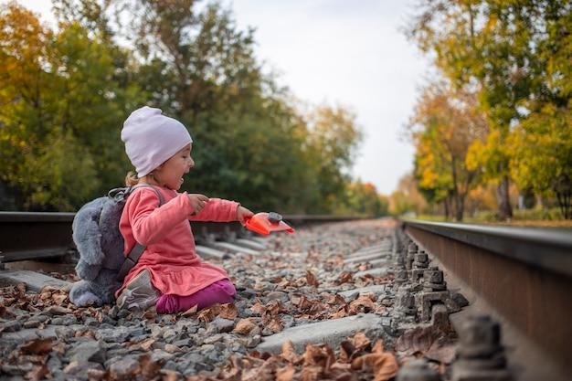 장난감이 아닌 귀여운 소녀의 게임은 버려진 철도 트랙에서 재생