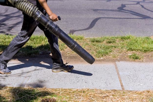 Садовник очищает воздуходувку для листьев на парковой дорожке с помощью садовых инструментов для создания потока воздуха.