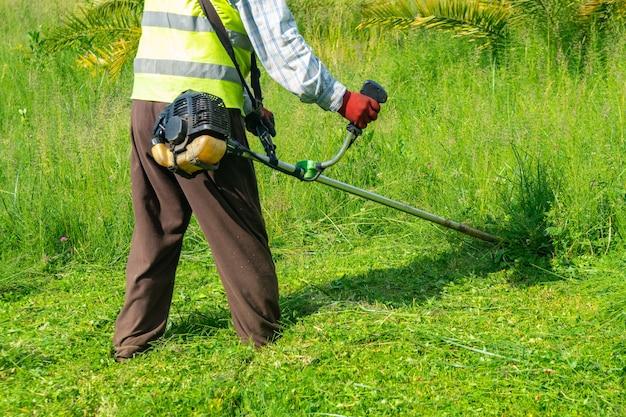 Садовник, косящий траву газонокосилкой