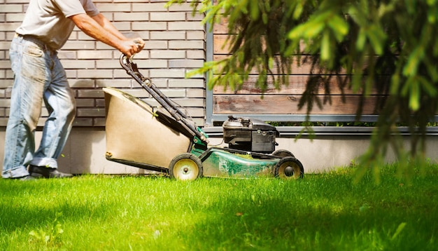 Садовник гоняет газонокосилку по двору.