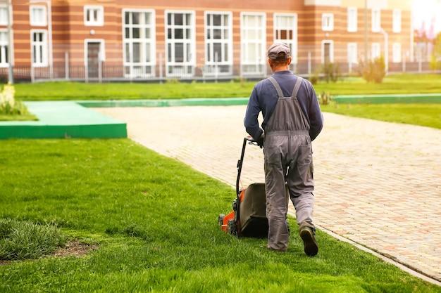 정원사는 잔디 깎는 기계를 밀고 있습니다. 잔디 깎기. 고품질 사진