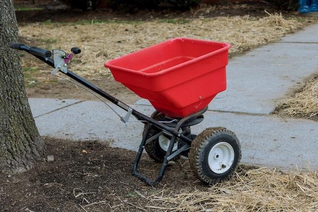 Садовник работает с посевом и удобрением газона, сеет свежую траву на заднем дворе жилого дома.