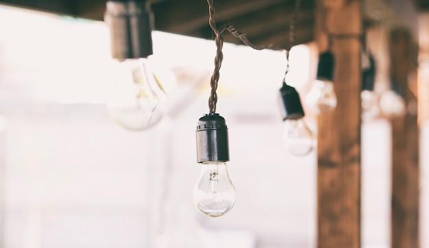 Гирлянда из лампочек висит на деревянной террасе
