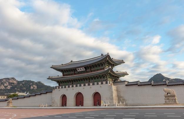 서울 한국의 구름과 푸른 하늘이있는 경복궁의 문