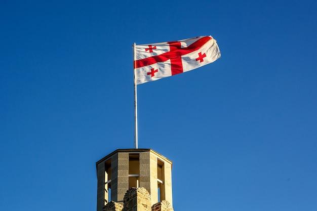 Флаг грузии на крыше древней башни на фоне ясного голубого неба.