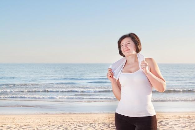 Девушка, спортсменка средних лет на пляже с полотенцем после тренировки ..