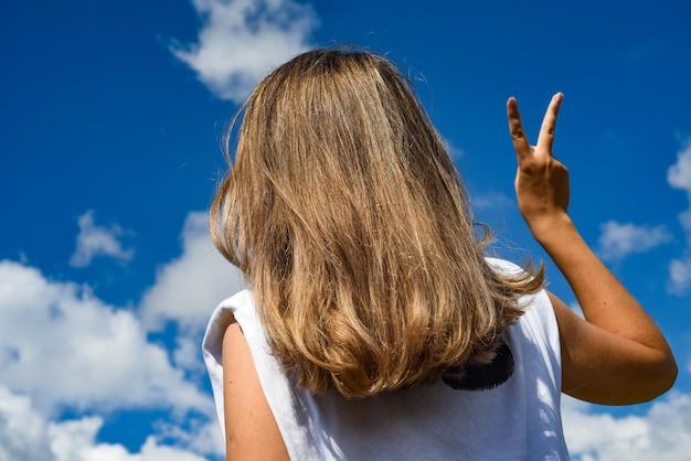 Девушка на фоне неба изображает руку победы