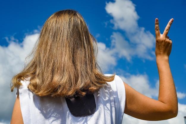 Девушка против неба делает победный жест