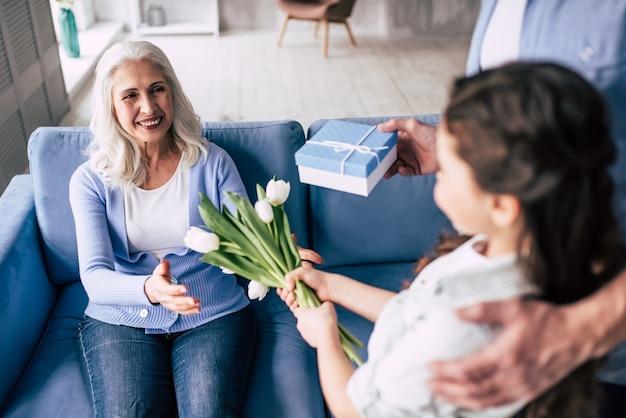 Девочка и дедушка дарят цветы и подарок бабушке