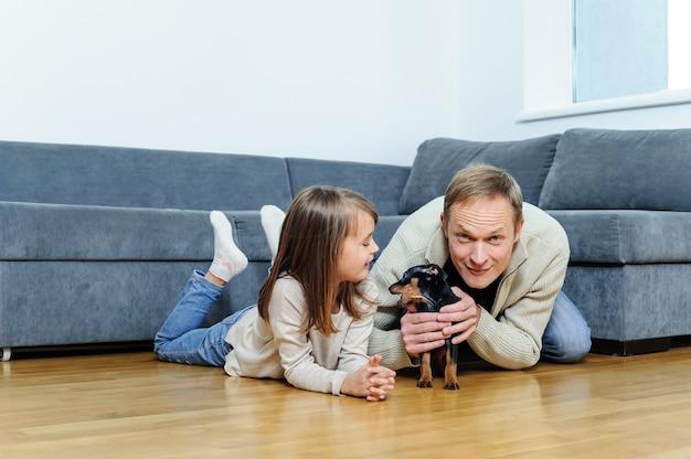 子犬を連れた女の子と男性が部屋の床にいます。