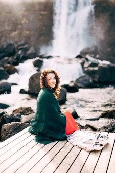 Девушка-художник пишет картину в альбоме акварельными красками возле водопада эхсараурфосс эхсарау