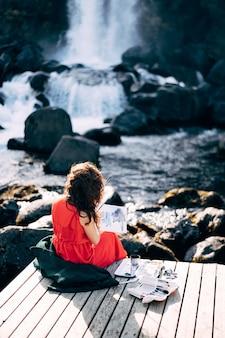 Ehsaraurfoss 폭포 ehsarau 근처에서 수채화로 앨범에 그림을 그리는 소녀 아티스트