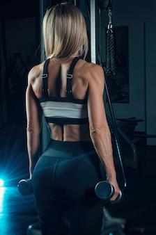 운동복을 입은 여자 운동선수가 체육관에서 훈련하고 있다