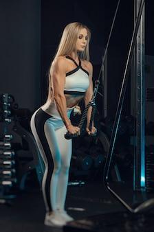 Девушка-спортсменка в спортивной одежде тренируется в тренажерном зале