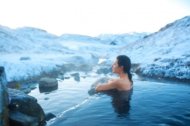 女の子は、雪山の素晴らしい景色を眺めながら、屋外の温泉に浸かります。冬の信じられないほどのアイスランド。