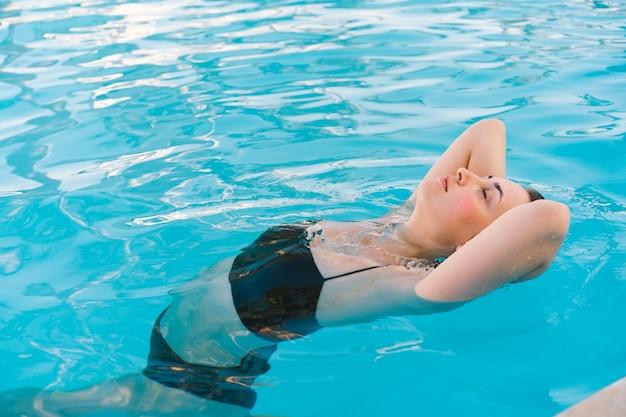 Девушка купается в бассейне. летние каникулы и путешествия.