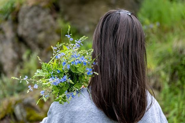 Девушка несет букет цветов, собранных в весеннем лесу, вид со спины.