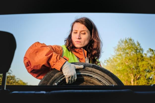 소녀는 자동차의 손상된 바퀴를 바꿉니다. 녹색 조끼 예비 바퀴 교통 사고