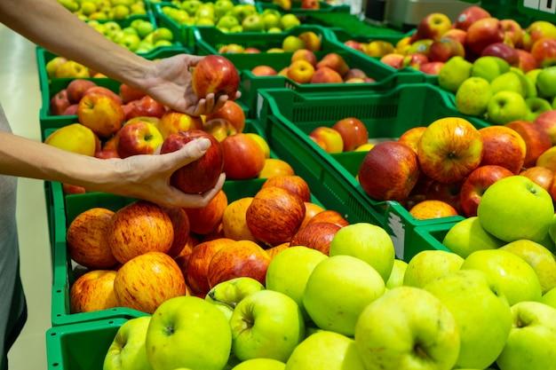 Девушка выбирает яблоки в супермаркете.