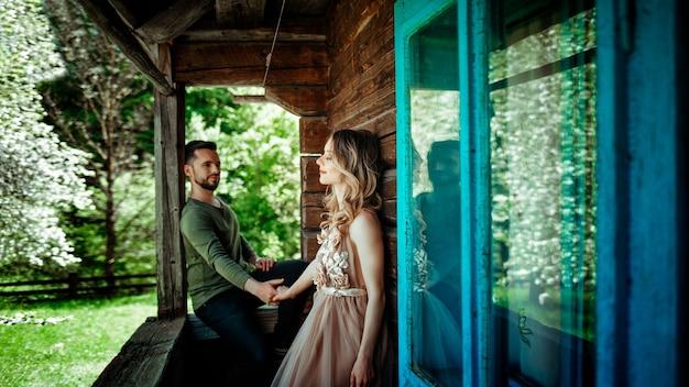 少女は目を閉じ、フツルの古い家のポーチに男を抱きしめます。緑と春をめぐるラブストーリーのコンセプト
