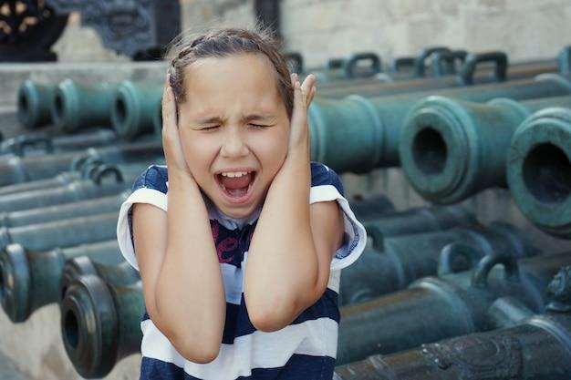 少女は両手で耳を掴み、古い大砲の銃身を背景に叫びました。