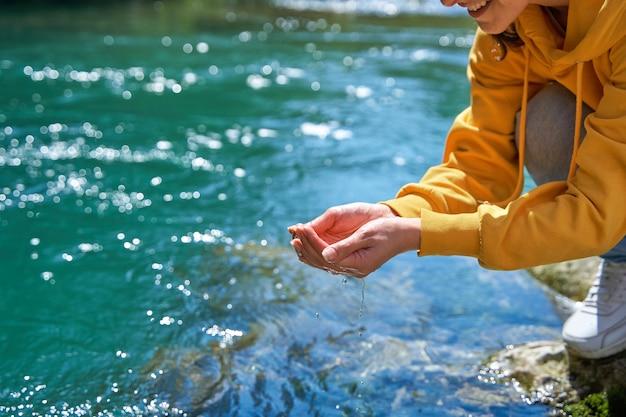 그 소녀는 손바닥에 산의 강에서 수정처럼 맑은 물을 모은다.