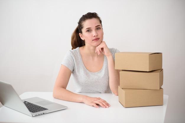 Девушка собирает заказы в картонных коробках. рядом находится стопка посылок на столе. концепция - служба доставки.