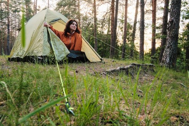 소녀는 자고 나서 텐트에서 나옵니다. 숲에서 도시 밖으로 여행. 캠핑.