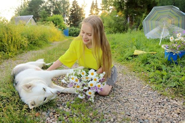 소녀는 여름에 그녀의 손에 데이지 꽃다발을 들고 사랑하는 개와 의사 소통합니다.