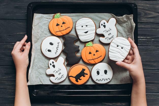 Девушка готовила пряники для хэллоуина и держала сетку с пергаментом на черном деревянном фоне.