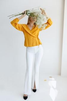 少女は乾いた花で顔を覆っている。ファッション写真。ムード