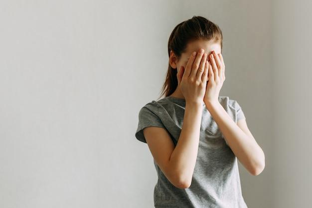 少女は手で顔を覆い、泣きます。女性に対する家庭内暴力をやめなさい。