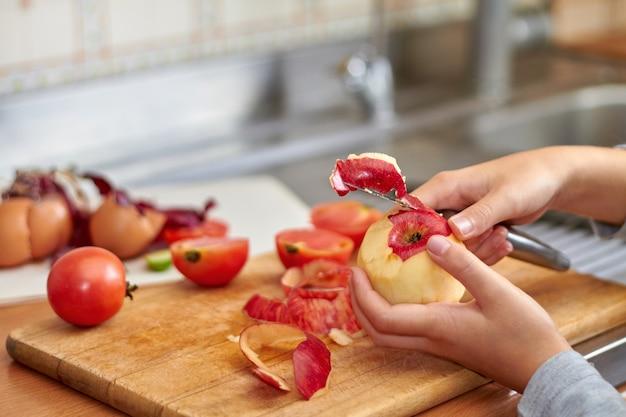 女の子は赤いリンゴからナイフで皮を切ります。台所で食べ物を準備している間の、食品廃棄物と端材。クローズアップ、セレクティブフォーカス