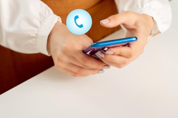 소녀는 전화가 들어오는 아이콘으로 스마트폰에서 전화번호를 다이얼합니다.