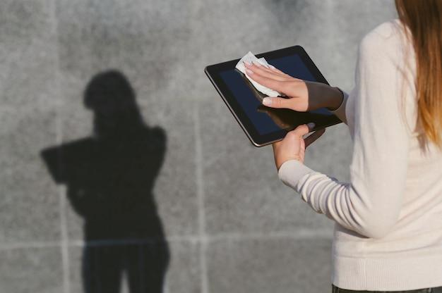 女の子はナプキンでピルを消毒します。灰色のコンクリートの壁を背景に、はっきりとした影のあるシルエットが残ります。