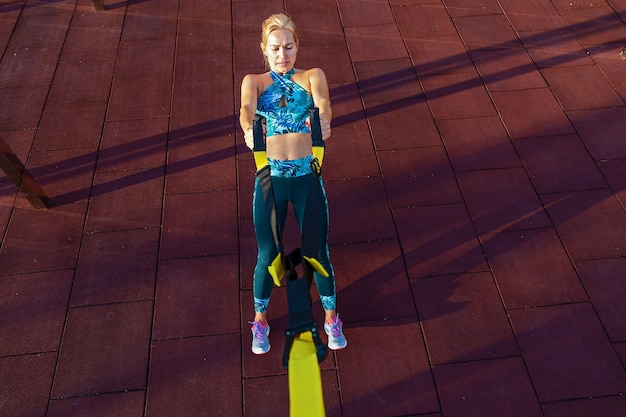 女の子は遊び場でフィットネスベルトtrxを使って運動をします。通りのフィットネス。スポーツフィールドでエクササイズをしている魅力的な女の子。フィットネスのためのスポーツウェア。ループを使ったフィットネスエクササイズ。癒し