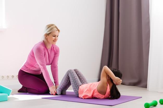 그 소녀는 집에서 체조를 한다. 체조 비디오 자습서. 체조 운동. 격리된 어린이 활동에 대한 아이디어