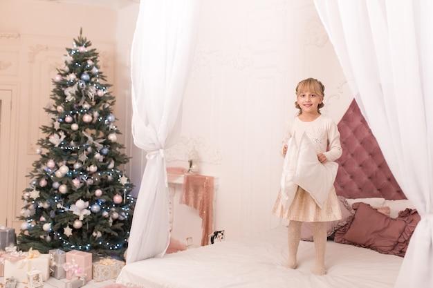 女の子はクリスマスの夜に眠りたくなくて、ベッドに飛び乗ります。