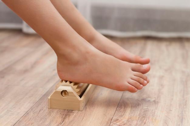 그 소녀는 평발, 외반을 예방하기 위해 특별한 나무 바늘 마사지기로 발을 셀프 마사지합니다. 다리의 이완.