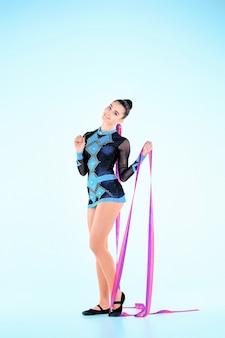 Девушка делает гимнастический танец с цветной лентой на синем фоне